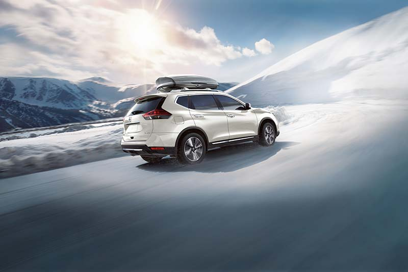 Nissan Rogue driving through snowy mountain
