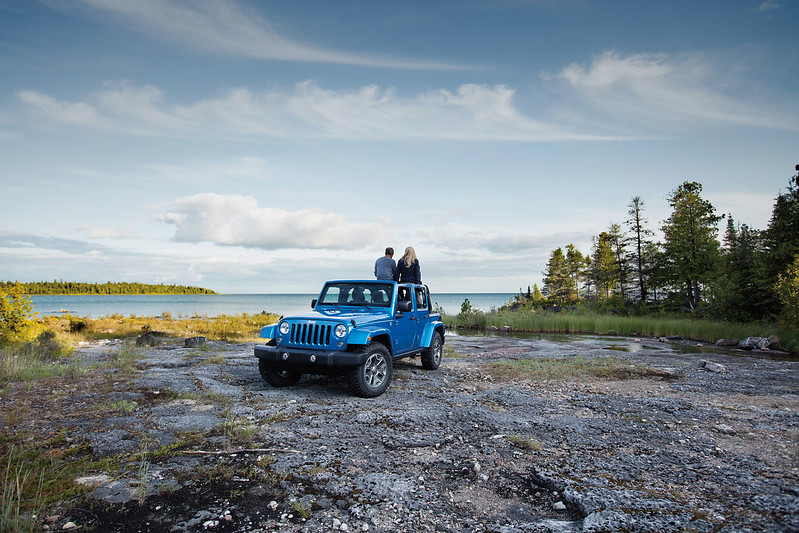 Couple sitting on Jeep® Wrangler Unlimited next to water