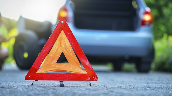 Hazard triangle on road with vehicle in background