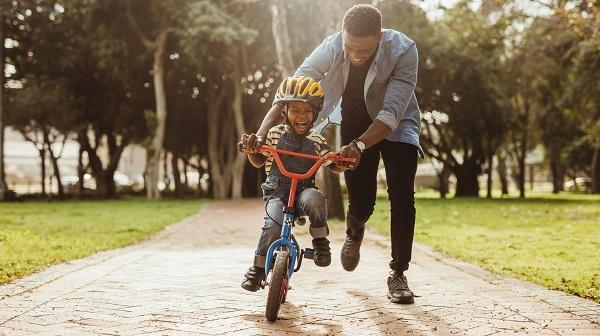 man helping child ride bicycle