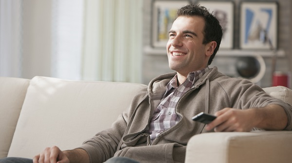 man sitting on couch watching tv