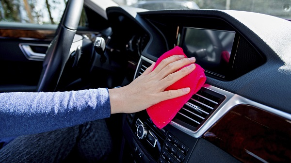 hand with rag cleaning car interior
