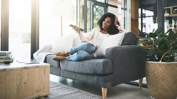 Woman Sitting on Couch Watching TV