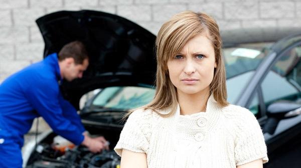 Upset woman standing in front of a broken down car