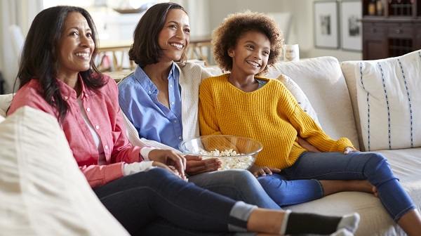 Mother, daughter, and grandmother watching television together
