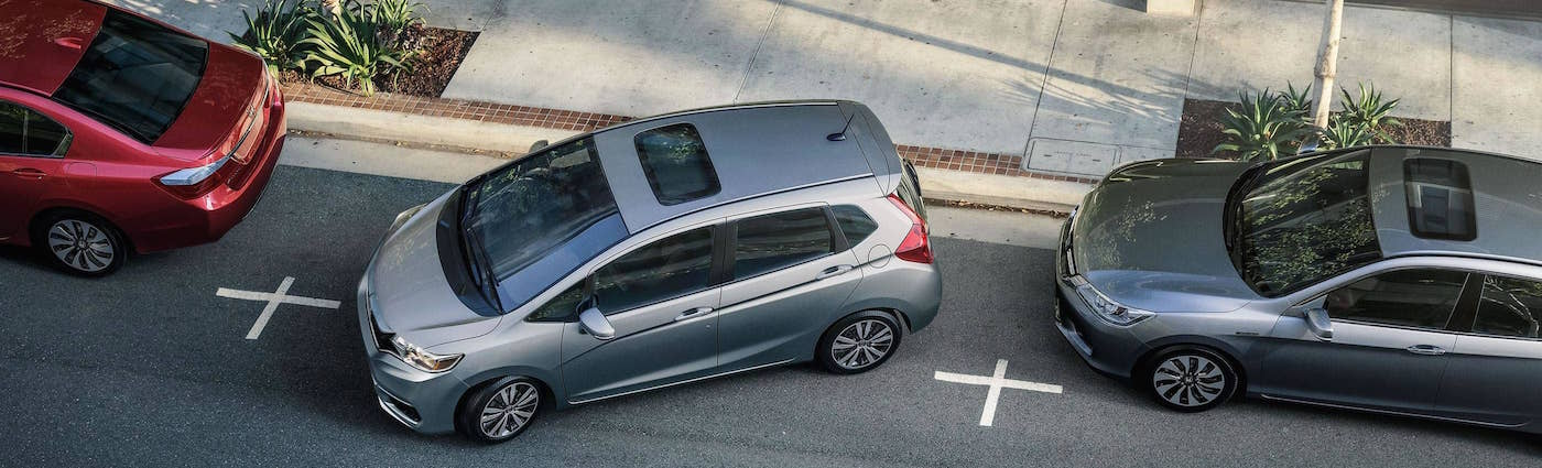 A grey 2018 Honda Fit parking on the street